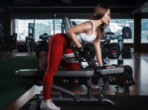 Woman exercising on a bench with dumbells